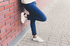 Girl Is Standing Near The Wall In Jeans And White Sneakers Stock Photos