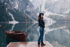 Free Girl Is Turned Side. Woman In Black Hat Enjoying Majestic Mountain Landscape Near The Lake With Boats Stock Image - 165450781