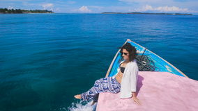 The girl on the island of Bali tours. She sits on the edge of the boat, admiring the turquoise ocean and clean. Just her stock footage