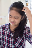 Young Girl Itching Scalp In Bedroom. Girl Itching Scalp In Bedroom stock photography