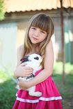The girl and its fluffy friend. The girl with sad eyes holds on hands of a rabbit royalty free stock image