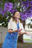 Girl and Jacaranda Tree. Pretty young girl happily throwing some purple jacaranda flowers from a tree in her hands Stock Photos