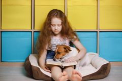 Girl and jack russell reading the book. Stock Photos
