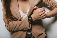 The girl in a jacket with a clock on her hand royalty free stock photo