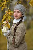 Girl in a jacket and hat against a tree with autumn leaves Stock Photos