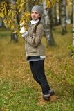 Girl in a jacket and hat against a tree with autumn leaves Royalty Free Stock Photos