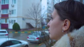 Girl in a jacket with a hood with a haircut looks to the side stock footage