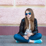 Girl in jacket, jeans and sunglasses sitting on pavement Stock Photo