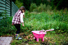 Girl in jacket playing in the garden with leaves Royalty Free Stock Photos