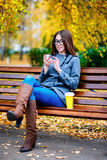 Girl in jacket sitting on the bench with glasses, holding a coffee or tea, young outdoors, spring fall, life style, t. Girl in jacket sitting on the bench with stock photography