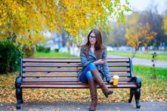 Girl in jacket sitting on the bench with glasses, holding a coffee or tea, young outdoors, spring fall, life style, t. Girl in jacket sitting on the bench with royalty free stock photography