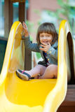 Girl in jacket on slide Royalty Free Stock Photos