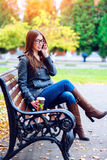 Girl in jacket talking on the phone, sitting  a bench, holding  coffee or tea,  young outdoors, spring  fall, life s Stock Photos