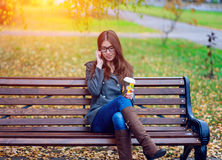 Girl in jacket talking on the phone, sitting  a bench, holding  coffee or tea,  young outdoors, spring  fall, life s Stock Photo