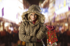 Girl in jacket winter with shopping bag. Attractive blond woman with shopping bag covering her head with hood from winter Stock Image