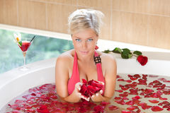 Girl in jacuzzi. Happy girl in jacuzzi holding a rose petals Royalty Free Stock Photos