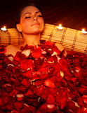 Girl in jacuzzi with rose petal and candle. Beautiful girl in jacuzzi with rose petal and candle. Body care Royalty Free Stock Photography
