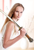 Girl with japanese sword. Blond girl with japanese sword royalty free stock image