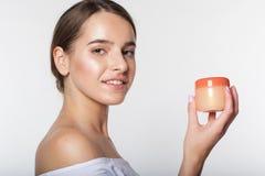 Girl with jar of facial moisturizing cream Royalty Free Stock Image