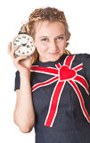 Girl in jean dress with alarm clock. Stock Photos