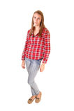 Girl in jeans. A young woman with long brunette hair standing in the studio in jeans and a checkered red shirt, for white background royalty free stock photo