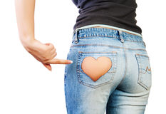 Girl in jeans. With heart-shaped hole on the buttock, indicates the finger Stock Photography