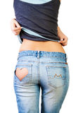 Girl in jeans. With heart-shaped hole on the buttock, removes a T-shirt stock photos