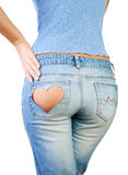Girl in jeans. With heart-shaped hole on the buttock, hand on hip royalty free stock photography