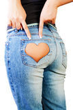Girl in jeans. With heart-shaped hole on the buttock, indicates the two fingers stock photo