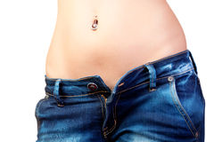 Girl in jeans. The young woman in unbuttoned jeans with a naked stomach and piercing Stock Photo