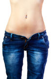 Girl in jeans. The young woman in unbuttoned jeans with a naked stomach and piercing Royalty Free Stock Photos