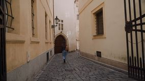 Girl in jeans and with backpack is walking along beautiful narrow old street. There is street lamp on wall, arch which