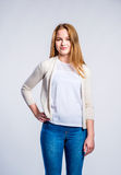 Girl in jeans and beige cardigan, woman, studio shot Royalty Free Stock Photos