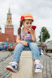 Girl in jeans and cap near the Kremlin sitting. The little girl in jeans and cap near the Kremlin sitting on concrete and looking into phone in hand royalty free stock photography