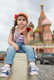 Girl in jeans and cap near the Kremlin sitting. The little girl in jeans and cap near the Kremlin sitting on concrete with a phone in hand royalty free stock photos