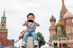 Girl in jeans and cap near the Kremlin sitting. The little girl in jeans and cap near the Kremlin sitting on concrete and takes pictures on the camera royalty free stock image
