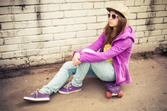 Girl in jeans, cap and sunglasses sits on a skateboard Royalty Free Stock Images