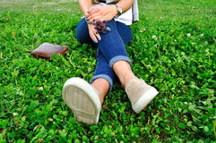 Girl in jeans in casual flats resting on green grass Royalty Free Stock Image