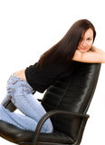 Girl in jeans on chair Stock Photography