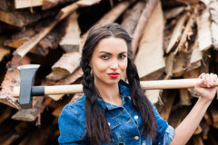 Girl in jeans clothes ax in hand. Beautiful girl in jeans clothes ax in hand Royalty Free Stock Photo