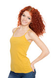 Girl in jeans with curly red hair. Royalty Free Stock Photography