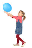Girl in jeans dress playing with balloon side view Royalty Free Stock Photography