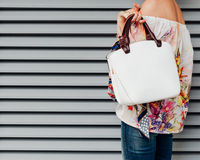 A girl in jeans and a fashionable colored blouse with a fashionable white handbag posing against a background of white Royalty Free Stock Photography