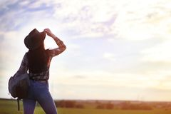 A girl travels the summer in the country. A girl in jeans and a hat travels the summer in the countryr Stock Photo