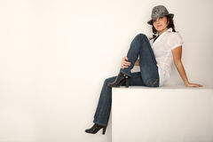 Girl in jeans, hat and white shirt sitting. In white studio. Horizontal format Stock Photos