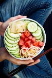 Girl in jeans holding hawaiian watermelon poke bowl with avocado, cucumber, mung bean sprouts and pickled ginger. Top view Royalty Free Stock Images