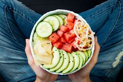 Girl in jeans holding hawaiian watermelon poke bowl with avocado, cucumber, mung bean sprouts and pickled ginger. Top view Stock Photo