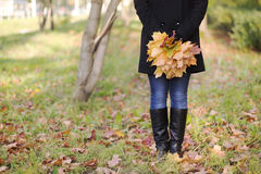 Girl in jeans holding a maple leaf. Girl in jeans and coat holding a yellow and green maple leaves Royalty Free Stock Images