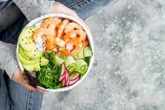 Girl in jeans holding shrimp poke bowl with seaweed, avocado, cucumber, radish, sesame seeds royalty free stock photo