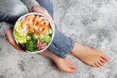 Girl in jeans holding shrimp poke bowl with seaweed, avocado, cucumber, radish, sesame seeds stock photo